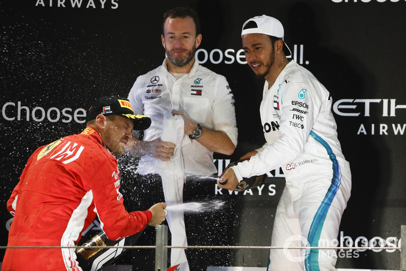 Sebastian Vettel, Ferrari, 2nd position, and Lewis Hamilton, Mercedes AMG F1, 1st position, spray Rose Water at each other on the podium