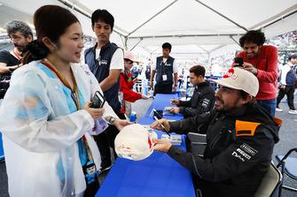 Fernando Alonso, McLaren, signs an autograph for a fan