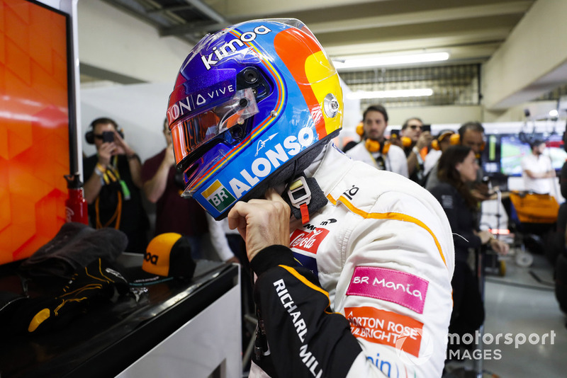 Fernando Alonso, McLaren, adjusts his crash helmet