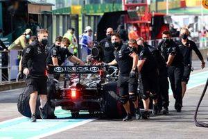 I meccanici spostano l'auto di Lewis Hamilton, Mercedes W12, in the pit lane
