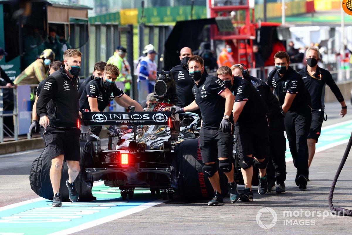 Los mecánicos mueven el coche de Lewis Hamilton, Mercedes W12, en el pit lane
