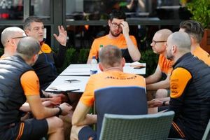 Members of the McLaren team hold a meeting in the paddock
