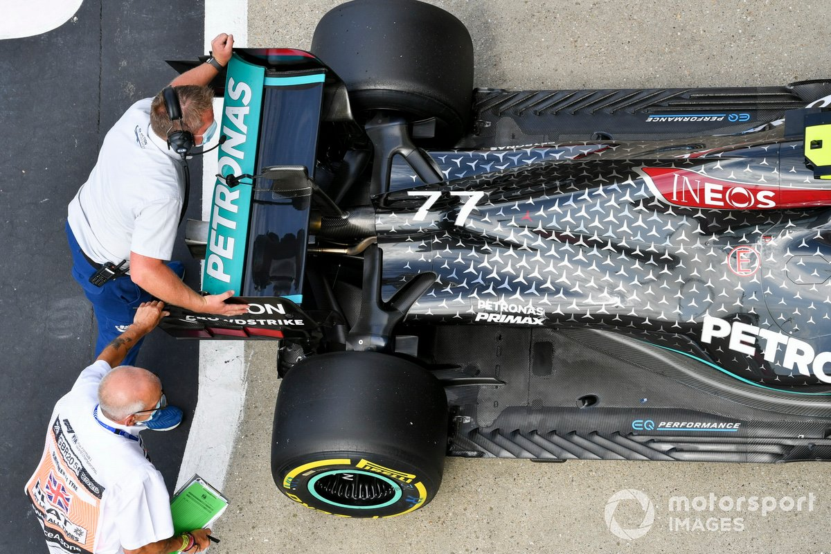 Los escrutadores mueven el coche del hombre de la pole Valtteri Bottas, Mercedes AMG F1, en el Parc Ferme