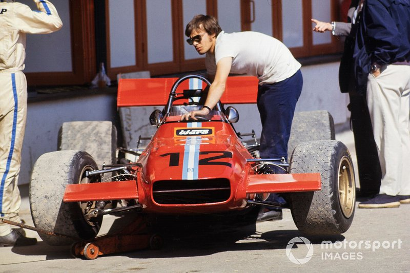 Piers Courage stands beside his De Tomaso 308 Ford in the pit lane