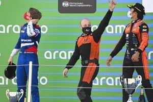 Robert Shwartzman, Prema Racing, 2nd position, and Nobuharu Matsushita, MP Motorsport, 1st position, on the podium as the MP team representative arrives