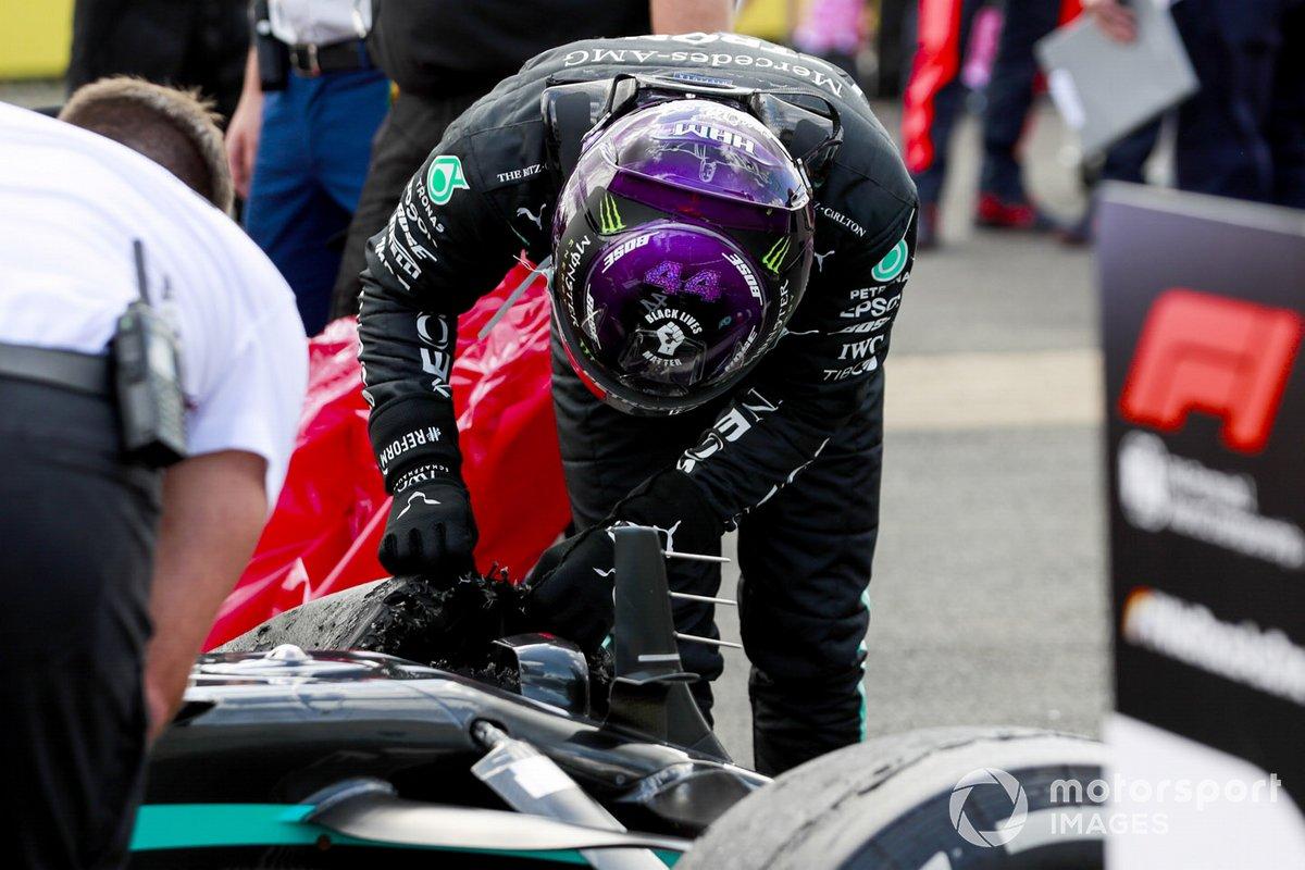Il vincitore Lewis Hamilton, Mercedes-AMG F1 controlla la gomma forata nel Parc Ferme