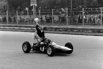 Jim Clark, Lotus 25 Climax gives team boss Colin Chapman a lift, as they celebrate finishing in 1st position and clinching the drivers and constructors World Championship titles
