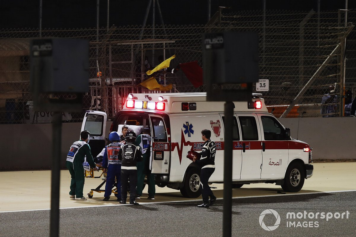 Medical delegates assist Romain Grosjean, Haas F1, after his first lap crash