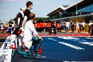 Sebastian Vettel, Aston Martin, and the other drivers stand and take a knee on the grid in support of the End Racism campaign
