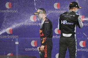 Juri Vips, Hitech Grand Prix, 1st position, and Oscar Piastri, Prema Racing, 2nd position, spray champagne on the podium