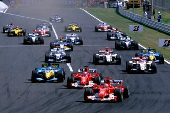 Michael Schumacher, Ferrari F2004 leads the field down to the first corner from the start