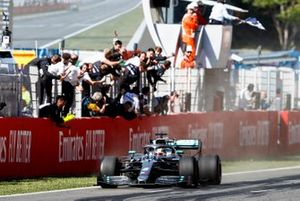 Race Winner drives over the Finish line with the checkered flag being waved with the Mercedes AMG F! Team celebrating