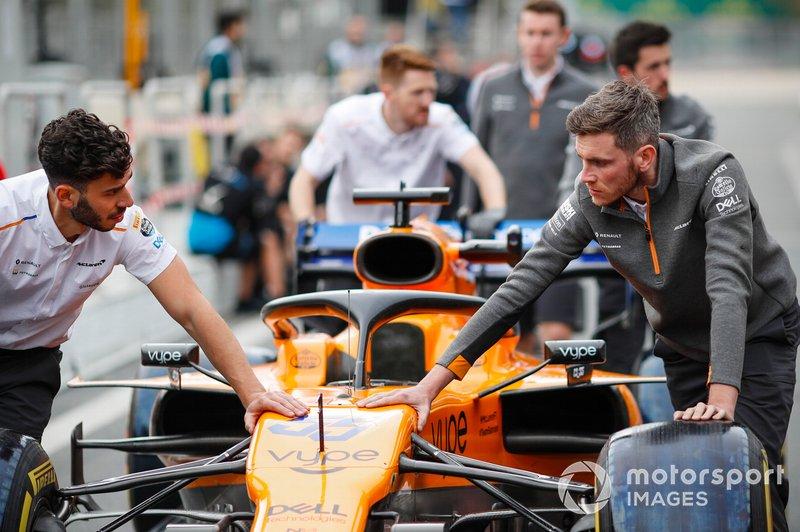 Un ingénieur de McLaren pousse la voiture de Carlos Sainz Jr., McLaren MCL34 dans la voie des stands