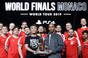 Formula 1 Driver, Lewis Hamilton and producer of Gran Turismo, Kazunori Yamauchi pose for a photo on stage with the competitors