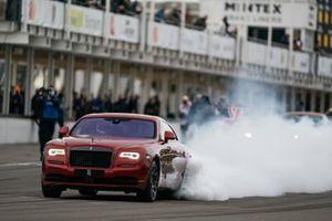A Rolls-Royce Wraith Black Badge burns rubber in the Supercar run