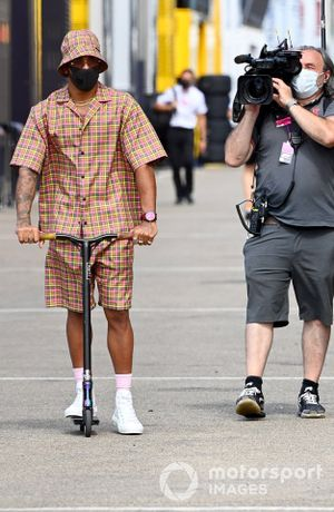 Lewis Hamilton, Mercedes-AMG F1, rides a scooter in the paddock