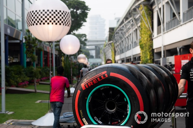Pirelli tyres are wheeled through the paddock by a Mercedes team member