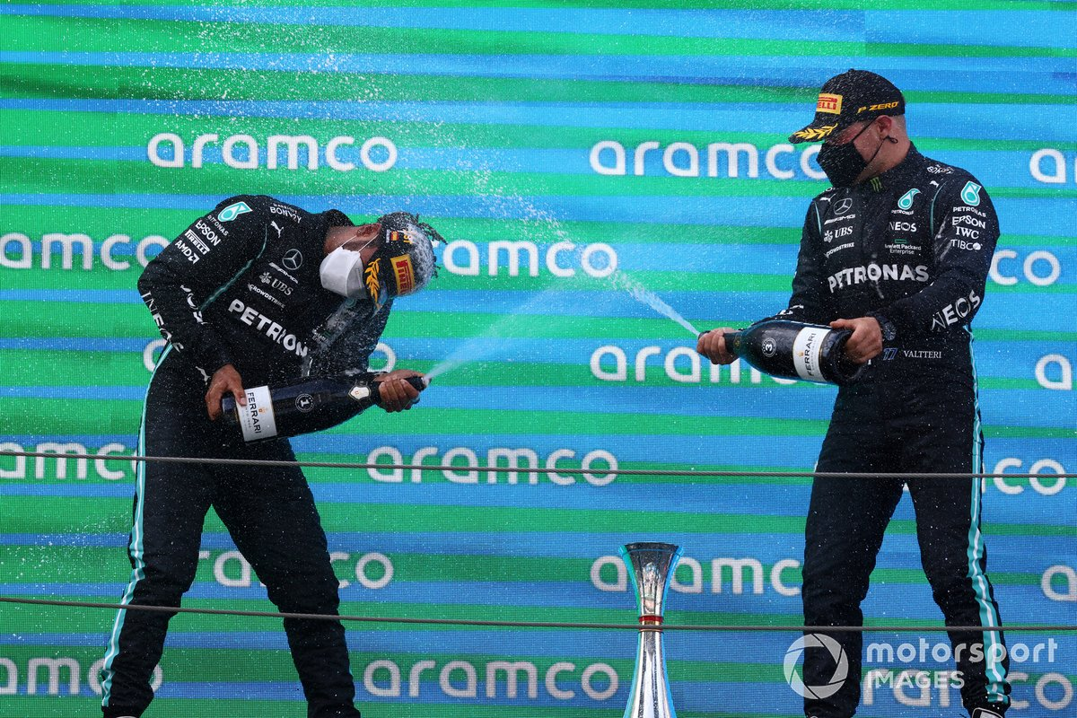 Lewis Hamilton, Mercedes, primera posición, y Valtteri Bottas, Mercedes, tercera posición, se bañan en champán en el podio