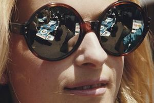 The Matra MS120 of Jean-Pierre Beltoise is reflected in a woman's sunglasses in the pits