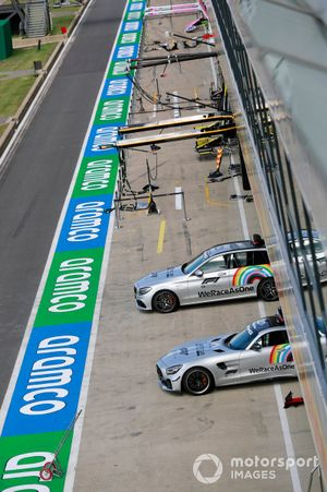 A Mercedes safety car and official car in the pit lane