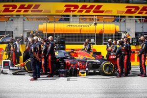 Red Bull mechanics and engineers stand around the car of Max Verstappen, Red Bull Racing RB16, on the grid
