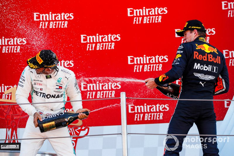 Lewis Hamilton, Mercedes AMG F1, 1st position, and Max Verstappen, Red Bull Racing, 3rd position, spray each other with Champagne on the podium
