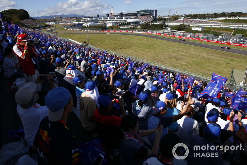 Fans with Toro Rosso flags wave as Brendon Hartley, Toro Rosso STR13, and Pierre Gasly, Scuderia Toro Rosso STR13, pass