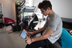 Lando Norris watches Autosport journalist Jack Benyon drive on his simulator