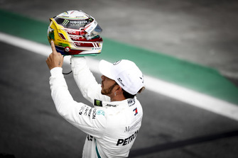 Pole man displays his special Senna colours helmet design to the crowd after Qualifying