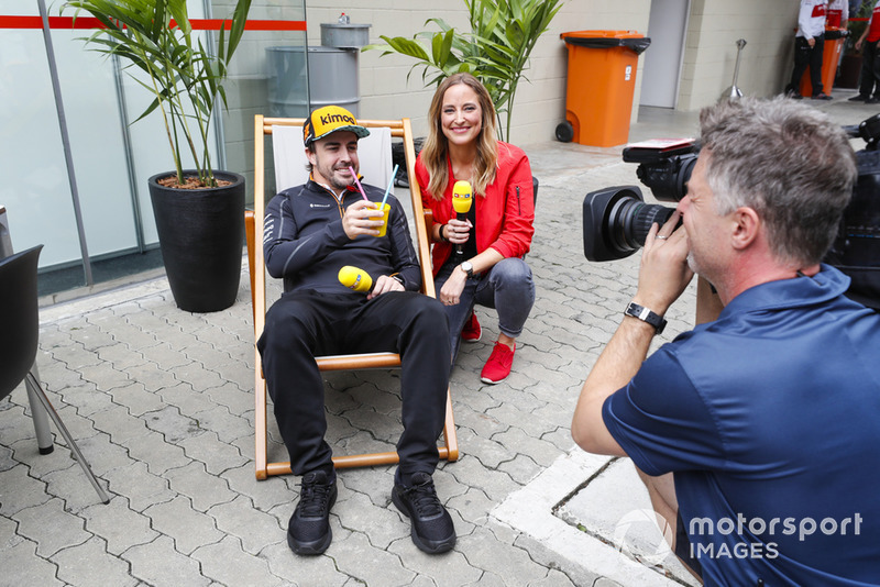 Fernando Alonso, McLaren, siede su una sedia a sdraio con un drink, accanto a una presentatrice RTL