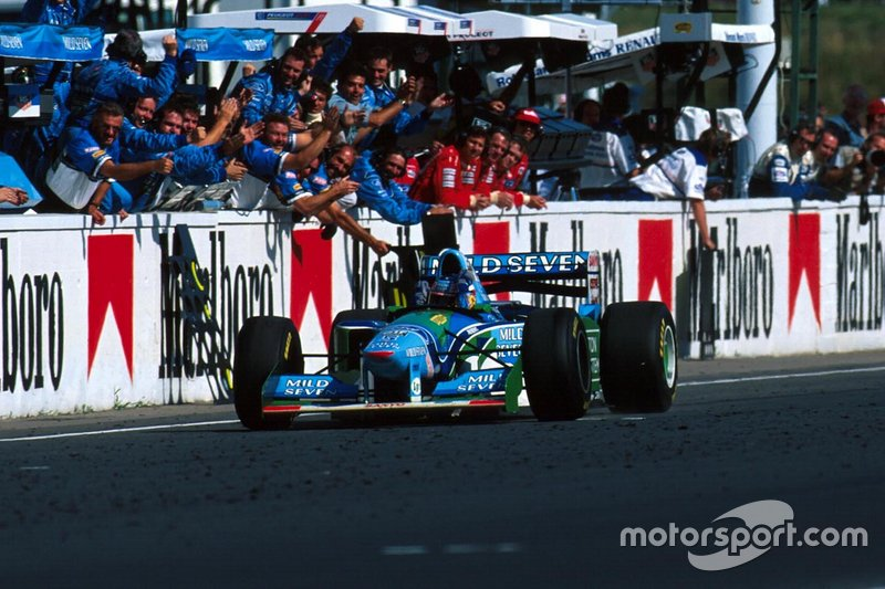 Michael Schumacher, Benetton B194, celebrates with the Benetton team as he crosses the finish line