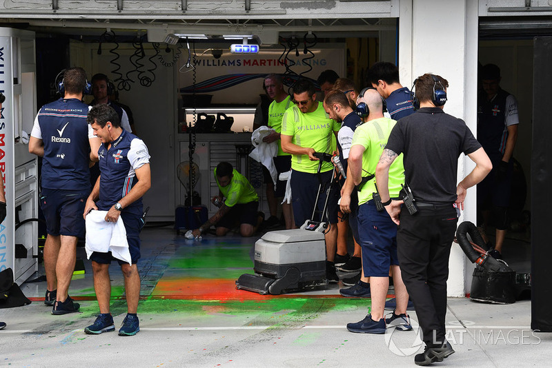 Williams mechanics clean aero paint from the garage floor