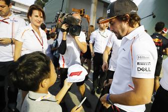 Fernando Alonso, McLaren, signs an autograph for a young fan