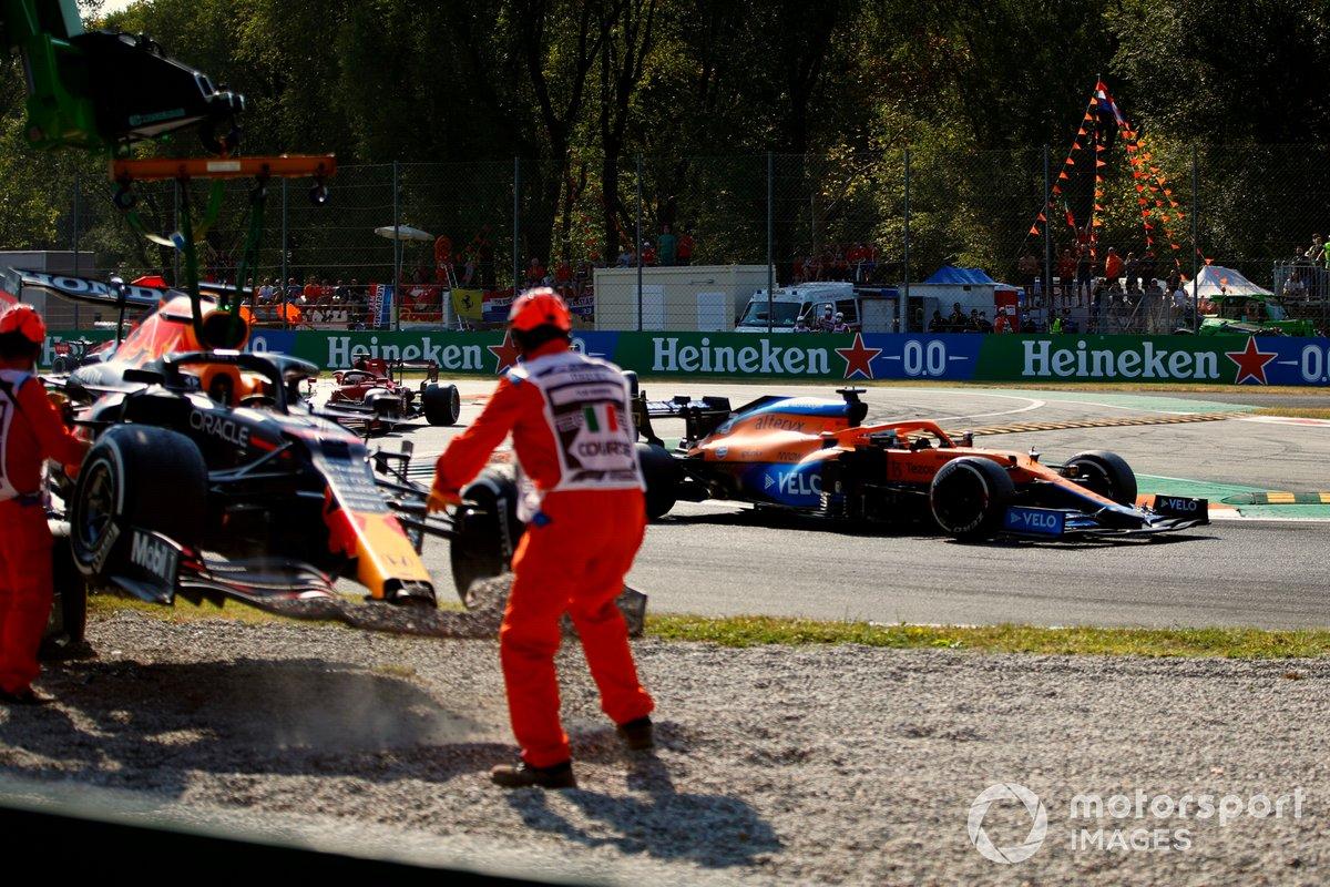 Daniel Ricciardo, McLaren MCL35M, pasa mientras retiran el coche de Max Verstappen, Red Bull Racing RB16B, de la grava