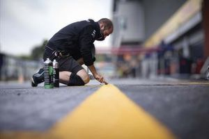 An AMG Mercedes F1 mechanic works in the pit lane