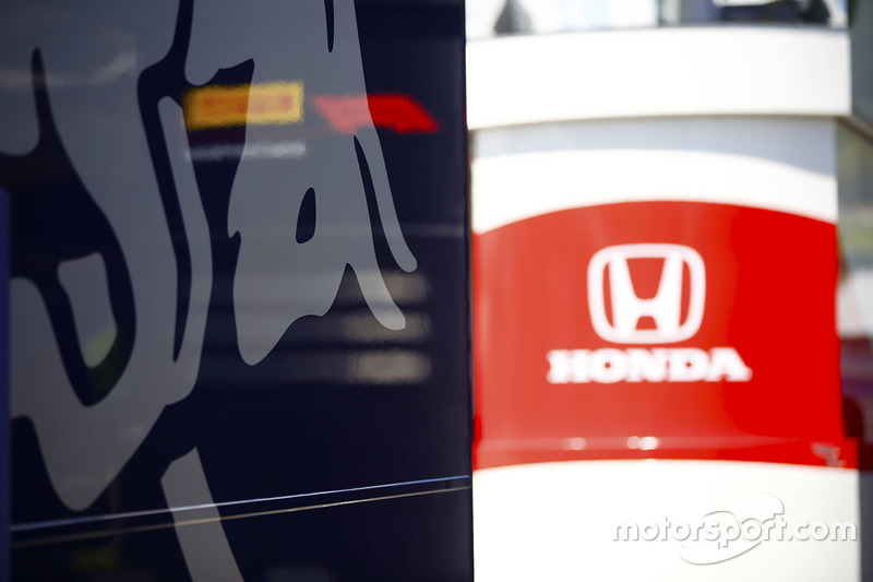 The Red Bull and Honda logos on trucks and hospitality units in the paddock
