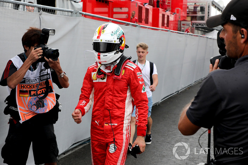 Sebastian Vettel, Ferrari walks in after crashing out of the lead of the race