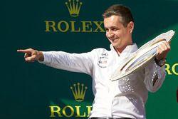 El delegado de trofeos de Mercedes Constructors celebra con el trofeo en el podio