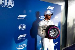 Lewis Hamilton, Mercedes AMG F1, holds a miniature Pirelli tyre after taking pole position