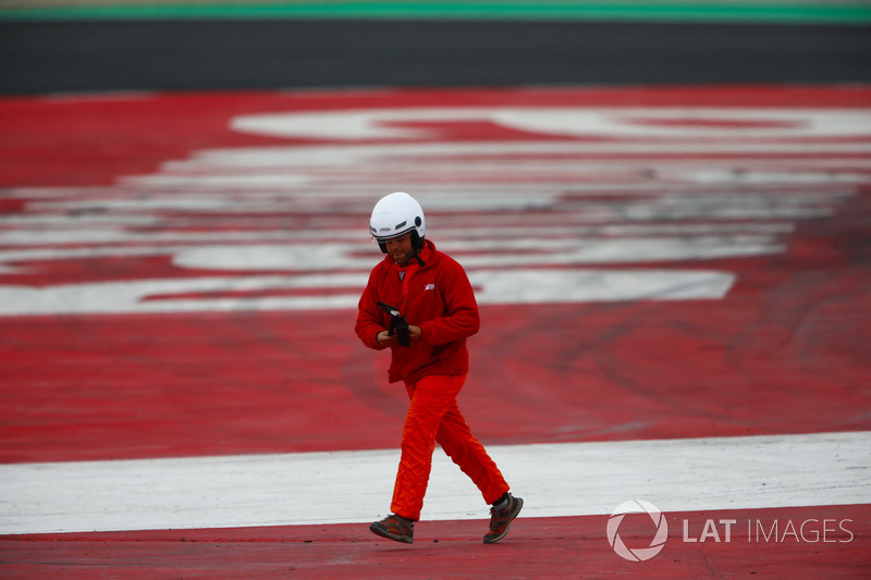 A marshal picks up a piece of debris from the track