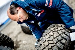 Peugeot Sport team member checks a tire