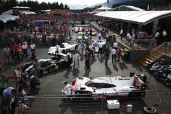 Brendon Hartley poses, a Porsche 919 sportcar. A Bentley, BMW V12 LMR, Group C Porsche, BMW CSL, Ferrari 512 and Porsche 917 line-up behind