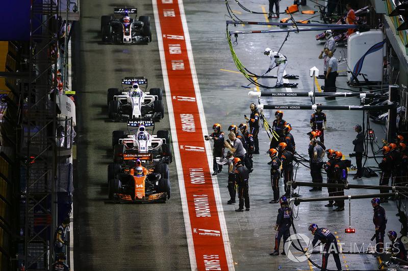 Fernando Alonso, McLaren MCL32 precede Lance Stroll, Williams FW40, Felipe Massa, Williams FW40 e Romain Grosjean, Haas F1 Team VF-17 ai box