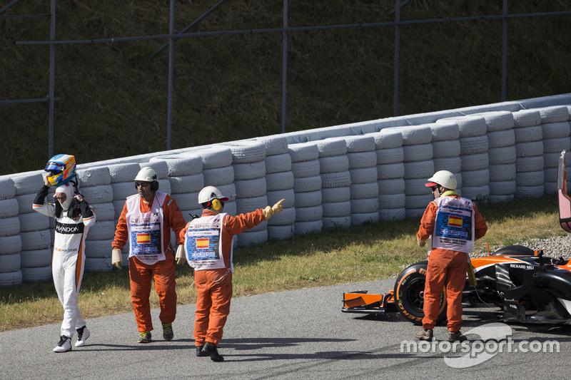 Маршалы помогают Фернандо Алонсо после отказа двигателя на его McLaren MCL32
