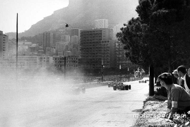 Les voitures passent au travers de la fumée après l'accident de la Ferrari 312 de Lorenzo Bandini.