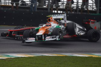 Nico Hulkenberg, Force India VJM05 Mercedes, slides into Lewis Hamilton, McLaren MP4-27 Mercedes, whilst attempting to pass for the lead