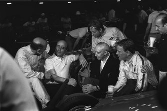 Stirling Moss in conversation with Juan Manuel Fangio with on-lookers Rene Dreyfus, Phil Hill, Dan Gurney and Maurice Trintignant