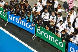 The Mercedes team gathers at the podium to celebrate