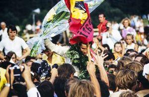Race winner Jacky Ickx celebrates at the podium ceremony