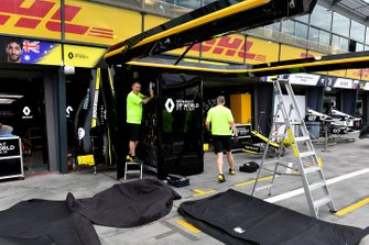 Renault personnel pack away their equipment in the pits